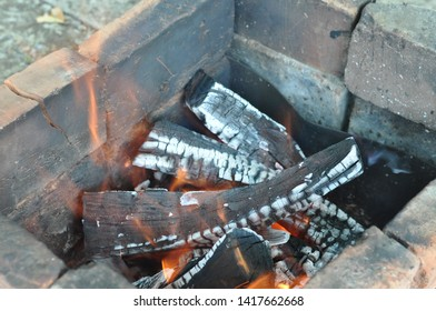 Smolder firewood with cracked surface covered by white ashes. Charred bricks in old mangal. Burning wood logs texture with blurry flames. Fiery background. Barbecue grill concept.