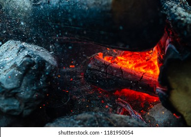 Smoldered logs burned in vivid fire. Atmospheric background with orange flame of campfire. Unimaginable detailed image of bonfire from inside with copy space. Whirlwind of smoke and ash close up.