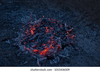 Smoldering ashes of a bonfire. Incandescent orange and red embers texture. Dark background.