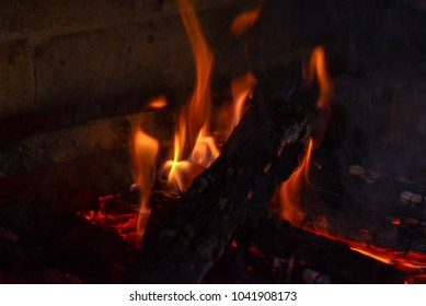 Smoldering ashes of a bonfire. Incandescent orange and red embers texture. Dark background. Fire flame and Firewood in a brick barbecue. A place for cooking meal outside.