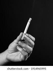 smoldering cigarette in female hand monochrome .