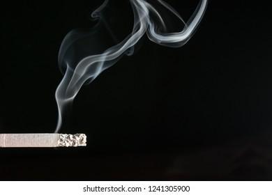 smoldering cigarette on a black background close-up