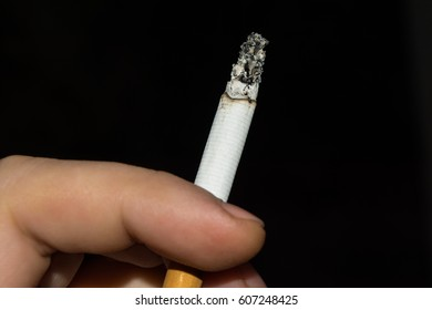Smoldering cigarette sandwiched between male fingers, black background