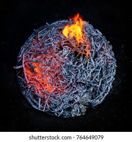 Smoldering fire in a round metal barrel after burning dry branches