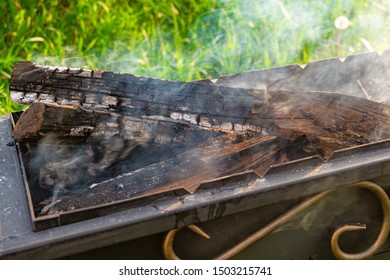 Smoldering firewood and embers in a steel barbecue