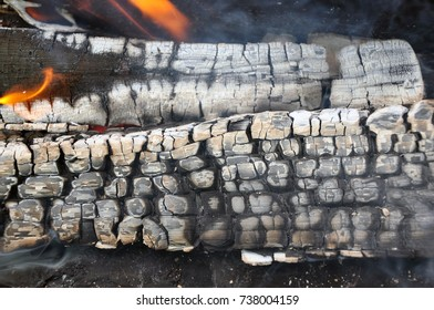 Smoldering firewood in the hearth.