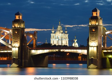 Smolny Cathedral in the alignment of Peter the Great Bridge on a June cloudy night. Saint-Petersburg, Russia