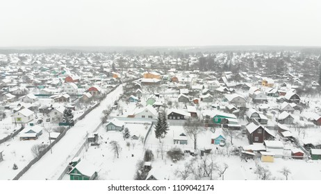 Smooth aerial shot above winter snowy forest, cold russian weather. Opening forward moving view at countryside village.