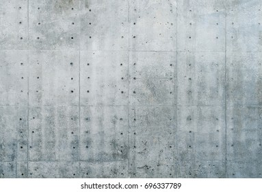 Smooth bare concrete wall with many concrete form dimples and grid lines.