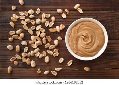 Smooth and creamy peanut butter and peanuts on wood table top.
