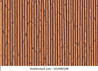 Smooth dark brown boards with knots. Background of wood slats. The texture of the wooden surface of the slats.