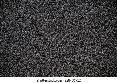 A smooth dark grey asphalt pavement texture with small rocks