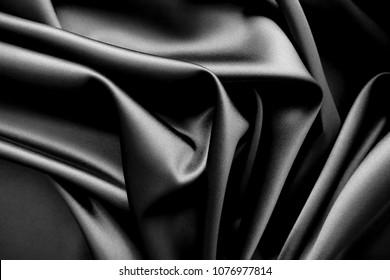 Smooth elegant black / dark grey satin silk  luxury cloth fabric texture, abstract background design. Copy space