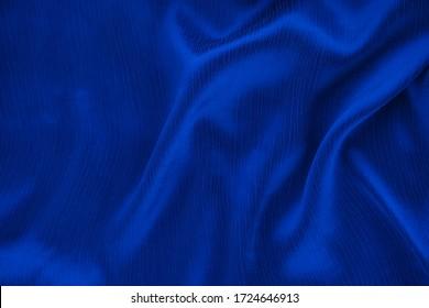 Smooth elegant dark blue silk textured background. Copy space.