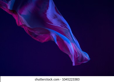 Smooth elegant transparent blue cloth isolated or separated on dark blue studio background. Texture of flying silk fabric.