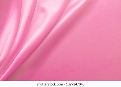 Smooth elegant wavy pink - pastel color silk or satin luxury cloth fabric texture, abstract background design. Can be used as Birthday, women's day or Valentine's day greeting card.