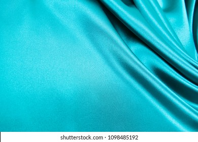 Smooth elegant wavy turquoise silk or satin luxury cloth fabric texture, abstract background design.
