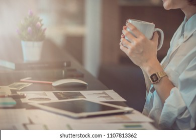Smooth Focus,A pretty businesswoman holds a white cup of coffee sitting at her office desk window to sip coffee in the morning before she starts working on documents and contacts business partners.
