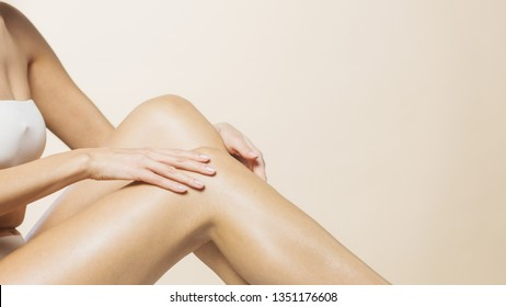 Smooth legs and hands touching and applying a lotion