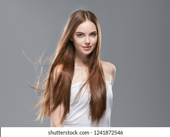 Smooth long brunette hair woman healthy and strong with healthy clean skin  female over gray background