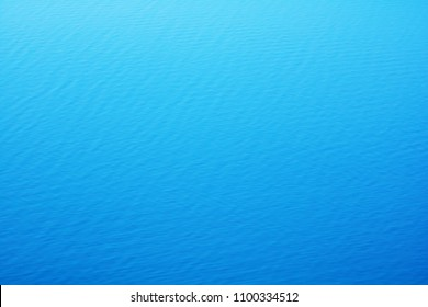 The smooth natural blue water background with bokeh  abstract on the sea or ocean,vintage and soft colored blur.