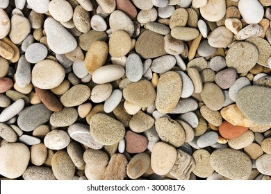 Smooth pebble background from a beach shore.