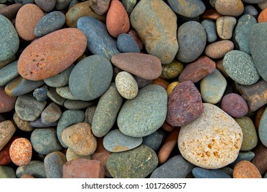smooth pebbles tumbled and polished on the beach textured background