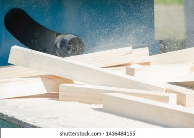 Smooth pine wood bars lie on a pile of sawdust and shavings. Pipe from a circular sawing table, from which shavings fly. Selective focus. Concept of carpentry, woodworking, handmade, male hobby