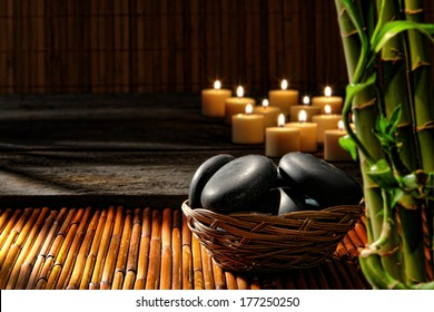 Smooth polished black hot massage stones in a basket with candles and bamboo stems in relaxing Zen inspired soothing atmosphere of wellness holistic spa for a natural well-being rejuvenation session