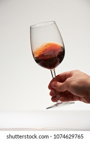 Smooth red wine surface in glass holding hand isolated on white background
