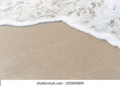 Smooth sandy at the beach and beautiful wave in background.