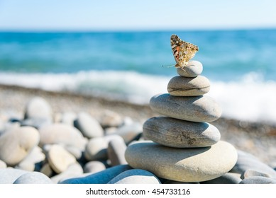 Smooth stones stacked on each other on the beach. Tower of stones for meditation on a sea. Moth sitting on top of the tower.
