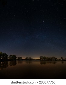 Smooth surface of forest lake on a background of the night sky and the Milky Way.