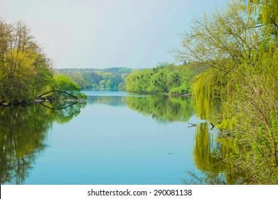 smooth surface of the river, on the banks of trees with light green leaves, the sky without clouds Spring