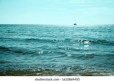 The smooth surface of the water and calm shining Waves. Little motorboat on horizon in  Bright green water. Sunset at The Lake Michigan. USA, Grand Haven.