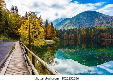The smooth surface of the water reflects the cloudy sky. The road around the lake Lago de Fusine, is fenced with wooden handrails. Concept of cultural and ecological tourism
