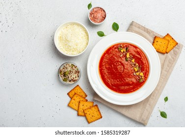Smooth tomato soup served with grated cheese and spicy crackers