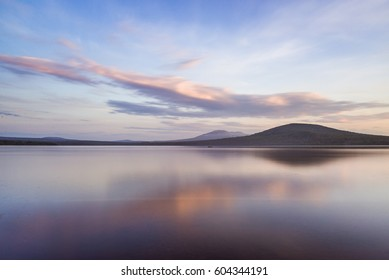 Smooth water surface with reflection in water at mountain background, Zyuratkul National Park, Russia