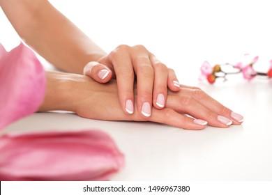 Leichte und gut befeuchtete weibliche Hände auf weißem Hintergrund.