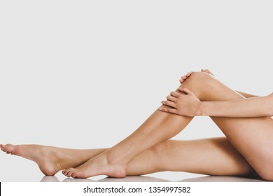Smooth woman's legs without cellulite on white background.