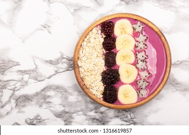 Smoothie or asai bowl on marble background. Decorated with berries, bananas, oatmeal, dragon fruit stars, chia seeds. Healthy breakfast concept. Flat lat, top view.