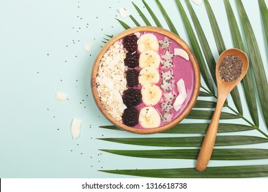Smoothie or asai bowl on mint color background. Decorated with berries, bananas, oatmeal, dragon fruit stars, chia seeds. Minimal composition. Healthy breakfast concept. Flat lat, top view.