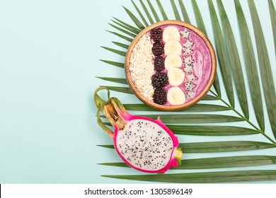 Smoothie or asai bowl on palm leaf. Mint color background. Decorated with berries, bananas, oatmeal, dragon fruit stars, coconut flakes. Healthy breakfast concept. Flat lat, top view.