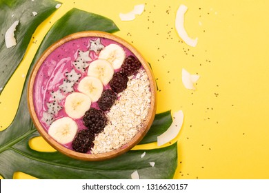 Smoothie or asai bowl on yellow background. Decorated with berries, bananas, oatmeal, dragon fruit stars, coconut flakes. Healthy breakfast concept. Flat lat, top view.
