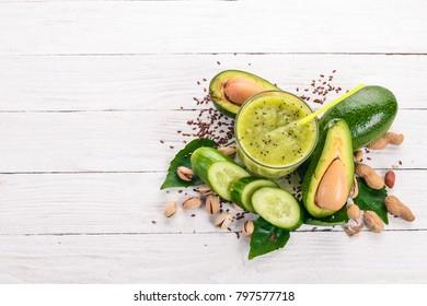 Smoothie with avocado and cucumber with flaxseed and nuts. On a wooden background. Top view. Free space for your text.