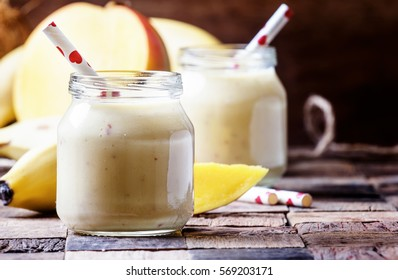 Smoothie with banana, cream and mango, rustic style, selective focus