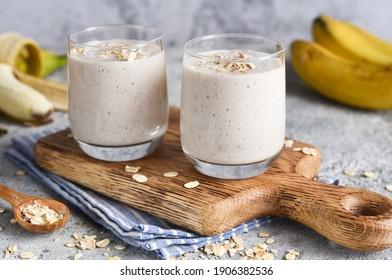 Smoothie avec banane et avoine pour le petit-déjeuner sur fond béton clair. Menu de la boîte de dialogue