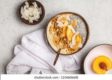 Smoothie bowl with chia pudding, peach, coconut and granola in a coconut bowl on white backgroud, top view. Vegan healthy breakfast, clean eating concept.