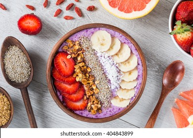 Smoothie bowl with chia seeds, muesli, strawberries, banana slices and coconut flakes