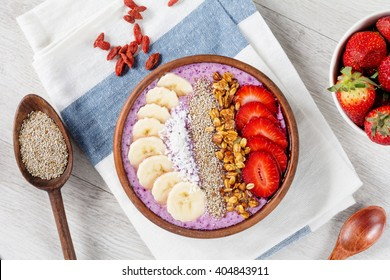 Smoothie bowl with chia seeds, muesli, strawberries, banana slices and coconut flakes, table top view. Healthy breakfast concept